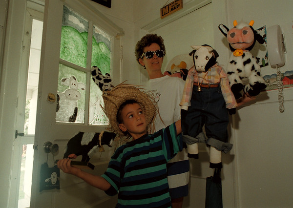 98/07/24 Cow Fetish - James Neiss Photo - Wendy Laprade and son Gregory 7yrs, show of just a few of the cows clutering up her kitchen. Included is a cow painted back door window.