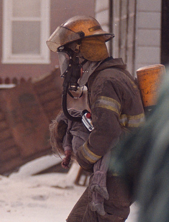1/29/96 Fatal Fire 6 - James Neiss Photo - Fire Fighter Aaron Shiah carries the limp body of a unconcious girl from the house fire at 915 Ceder Ave.