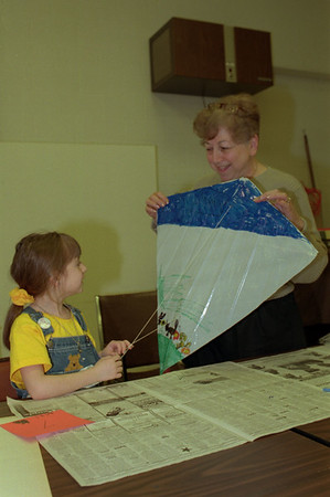 98/04/14 Go Fly A Kite *Dennis Stierer photo - Go Fly A Kite was the theme at the Dale Association this morning as Grandparents and Grandkids got together to color and build their own kite. Here 6 year old Niki Micoli puts the finishing string on her kite as grandma, Jolene Micoli helps steady the kite.