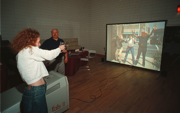 5/14/97 Firearms Training - James Neiss Photo - Citizens Police Academy -  Lauras Burbee 19yrs of NF, an Americorp member, gets some shooting tips from Niagara Falls Police Frire Arms instructior Robert Gee. They were training using F.A.T.S (Fire Arms Training System) at the Summit Park Mall.