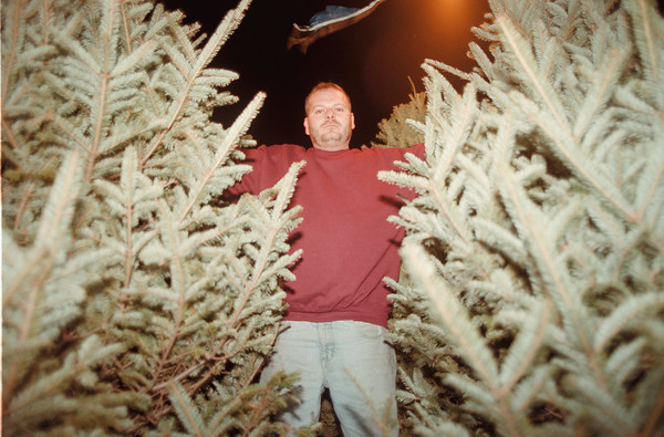 98/12/10 Mike Kornaker - Vino Wong Photo - Mike Kornaker stands by many of his Christmas trees for sale across from Target Town of Niagara Falls.