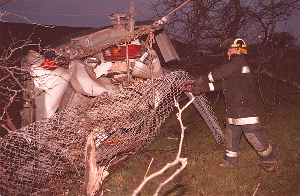 5/19/97--AUTO ACCIDENT--DAN CAPPELLAZZO PHOTO--A NIAGARA ACTIVE HOSE COMPANY FIRE FIGHTER CUTS A FENCE TO FREE THE TWISTED RUBBLE LEFT FROM A ONE CAR ROLLOVER CONTAINING 5 PASSANGERS ON PACKARD RD NEAR THE 190 OVERPASS.<br /> <br /> 1A NEWS
