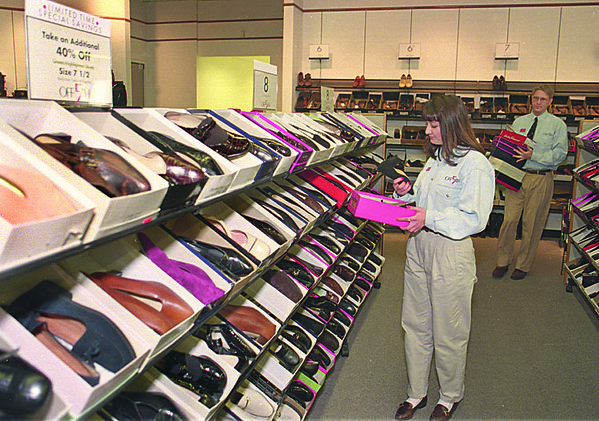 1/15/97--OUTLET/TAXES--CAPPY PHOTO--SALES ASSOCIATE ROMANY GIOVE CHECKS THE TICKETING ON SHOES, A TAX FREE ITEM ON THE WEEK OF JAN 18, AS SUPERVISOR ROB SPENCER BRINGS UP MORE STOCK TO KEEP THE SHELVES FULL FOR SATURDAY.<br /> <br /> 1A