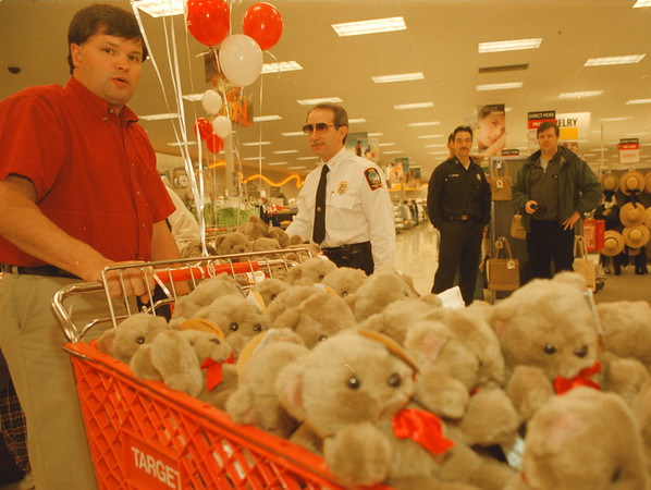 """98/02/21-- t. bear --Takaaki Iwabu photo-- Ben Gregory, left,  store team leader at TARGET on Niagara Falls Blvd, pushes the cart full of teddy bears as Nick Vilardo, Cheif of Fire Prevention, looks on.  TARGET gave away teddy bears to Niagara Falls Fire Department to help comfort children in emergencies as part of the store's """"Helping Hug"""" program. <br /> <br /> bw, Sunday, local"""