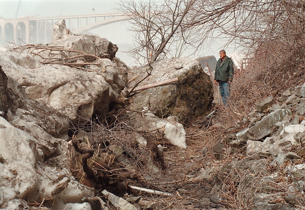 4/23/97 Cave of Winds Damage - James Neiss Photo - Bob Kesil, Cave of the Winds Facility Manager stands near a rock that was pushed by the ice pack up from the gorge onto the path tourists take to the falls viewing deck on the Cave of the Winds Tour.