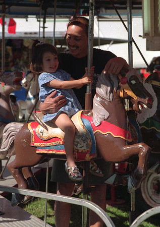 98/07/31 Merry-G0-Round *Dennis Stierer Photo - <br /> Leonard Wall takes his two year daughter, Sabrina on the merry-go-round at the Shawnee Feild day Festival going on through Saturday.