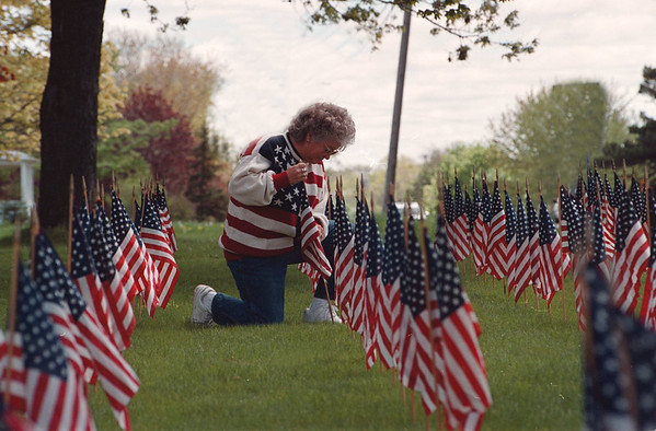 5/26/97--SANBORN HOLIDAY--DAN CAPPELLAZZO PHOTO--LINDA TREICHLER, OF 2687 SAUNDERS SETTLEMENT RD. PLACES ONE OF MANY FLAG IN HER FRONT YARD FOR THE MEMORIAL WEEKEND.<br /> <br /> 1A