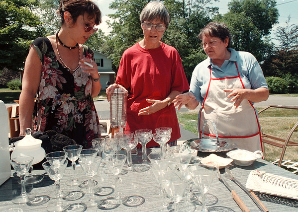 7/28/97--garage sale 3--tak photo-- Esther Bellitto, right, shows her offerings to garage sale shoppers Elle Ehrlich (left) and Judy Mangan in Villge of Lewiston.