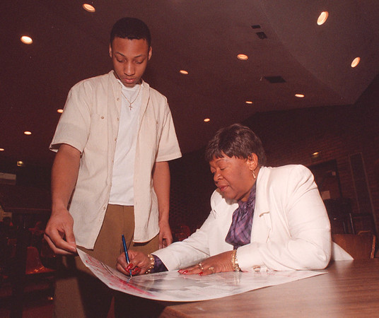 3/12/97 Olympian - James Neiss Photo - 3 time olympian speaks at Niagara University -  Mae Faggs - Starr signs a poster for Jeff Sturdivant of Niagara Falls High School who was attending her lecture. Faggs-Starr won the gold in the 400 meter relay in 1952 setting a new worlds record.