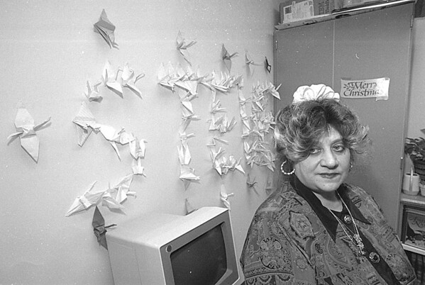 1/3/97 Steven McClinsey Story 6 - James Neiss Photography - Steven's mom, Anne Baker, sits near a collection of Origami Cranes spelling out Steven's name arranged by classmates.