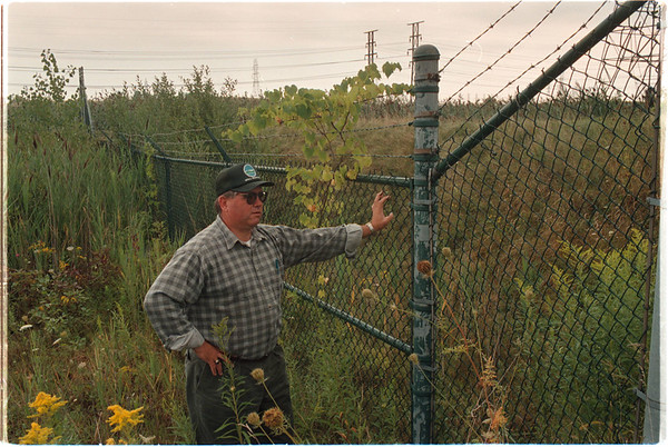 97/08/25 Raised Waterline - James Neiss Photo - Michael J. Hinton a Environmental Engineer with the NYS Department of Environmental Conservation looks through a fence at a mound covered raised waterline that skirts the border of the Union Carbide Landfill.