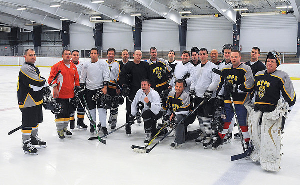 James Neiss/staff photographerNiagara Falls, NY - Lt. Dave Kok, captain of the Niagara Falls Police hockey team, left, stands with teammates for a photo at Hyde Park.
