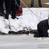 James Neiss/staff photographerNiagara Falls, NY - Niagara Falls Fire Battalion Chief Dan Boland crawls through the icy waters of Hyde Park Lake trying to reach Pascal Scrufari of Niagara Falls who fell through the ice. Fire Capt. Jason Zona stands by to assist. Two of Scrufari's three dogs look on.