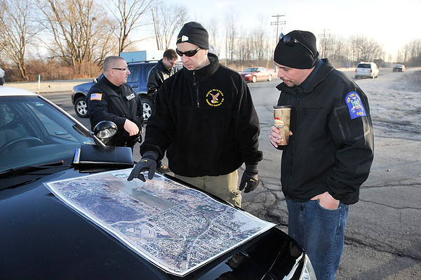 James Neiss/staff photographerNiagara Falls, NY - Officer David Bower, Detective Mark Jaroszewski and Bergholz Volunteer Fire Fighter Robert Blume look over a map of the search area.