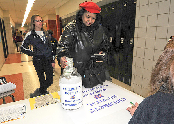 James Neiss/staff photographerNiagara Falls, NY - Shirley Cullins of Niagara Falls makes a donation during Children's Hospital Night at Niagara Falls High School before the basketball game between Niagara Falls and North Tonawanda.