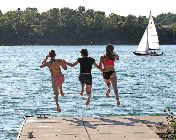 James Neiss/staff photographerYoungstown, NY - Girlfriends, from left, Kacey Ferry, 12 of Youngstown, Cassy Tierney, 13 of Niagara Falls and Mickayla McNamara, 12 of Youngstown, leap off the Youngstown Public Dock for a cool swim in the Niagara River.