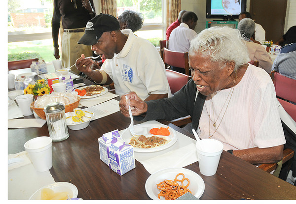James Neiss/staff photographerNiagara Falls, NY - Rosevelt Bradberry 71 and Emma Page, 96, enjoy a meal provided by the Niagara County Office for the Aging at the St. John's AME Church on Garden Avenue.  There is concern that the nutrition program there will end.