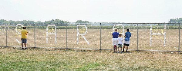 James Neiss/staff photographerWilson, NY - The community gathered to remember Sarah Johnson who died when her home exploded because of a propane leak. The memorial service was held at the Wilson Soccer Complex where those attending were given a yellow ribbon to tie onto a fence with her name spelled on it.