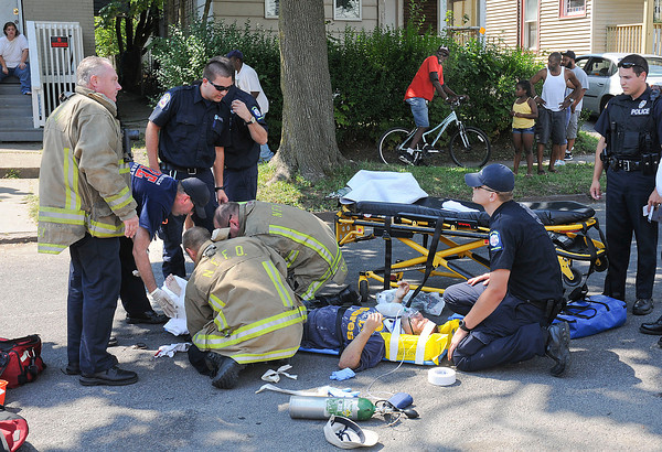 James Neiss/staff photographerNiagara Falls, NY - Emergency responders prepare a man to be transported to the hospital with a leg injury after being hit by a car on Ashland Avenue near 15th Street.