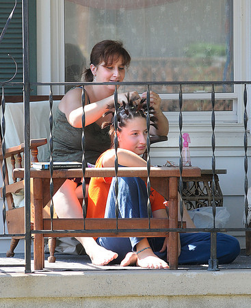 James Neiss/staff photographerWilson NY - Elizabeth Schearer, 14, gets her hair set with the help of her mother Dina, in front of their Lake Street home. Elizabeth is heading into the 8th grade this year and hoped that when the rubber bands come out, her hair will be neatly styled.