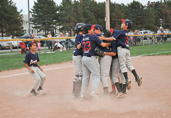 James Neiss/staff photographerNiagara Falls, NY - The MacLeod's Pharmacy Braves celebrate after winning the city championship game against the Tops Tigers at Nicoletti Field.