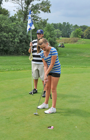 James Neiss/staff photographerNiagara Falls, NY - With help from her brother Matthew, 14, holding the flag, Madison Townsend, 12 of Wheatfield, putts in her last ball during the 35th Annual City of Niagara Falls Junior Golf Tournament at Hyde Park on August 14. Officials, said that the tournament was a big hit with about double the participants this year.