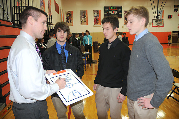 James Neiss/staff photographerWilson, NY - Coach Brett Sippel talks to captains Geoff Lort, Liam McIntosh and Matt Baker before a game against Lew-Port.