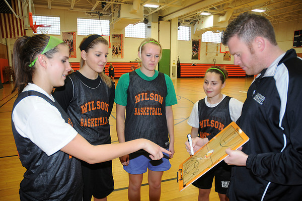 James Neiss/staff photographerWilson, NY - Wilson girls basketball captains Emily Lasher, Jamie Curry, Kate Placek and Mallorie Gagnon talk shop with coach Brian Baker during practice.