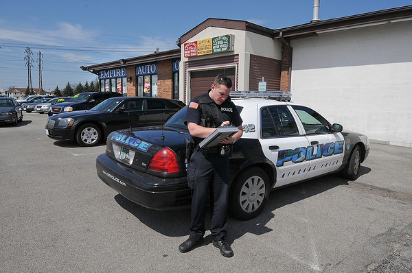 James Neiss/staff photographerNiagara Falls, NY - Niagara Falls Police Officer Patrick Clifton assists in the police report for a robbery at Empire Auto Outlet on Niagara Falls Boulevard.