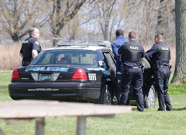 James Neiss/staff photographerNiagara Falls, NY - Niagara Falls Police Officer put a suspect into a car after a robbery at Empire Auto Outlet on Niagara Falls Boulevard and a foot chase into Hyde Park.