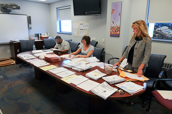 James Neiss/staff photographerNiagara Falls - Niagara Street Elementary staff, from left, Rutherford Watson, Ashley Rotella and Diane Bianco, organize completed state tests.