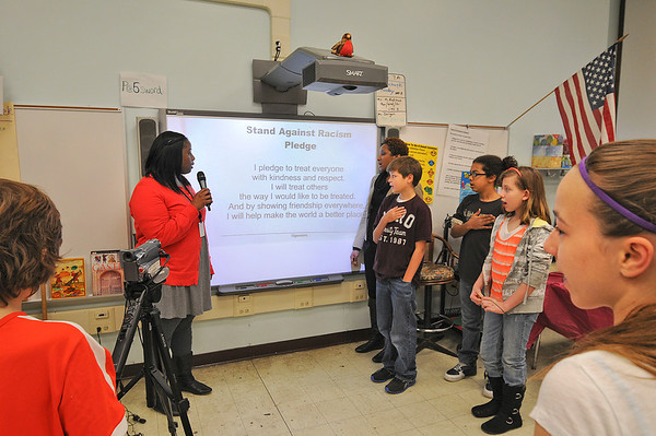 James Neiss/staff photographerNiagara Falls, NY -  The Maple Morning Show hosts, from left, School Counselor Ebone Bradberry, Pupil Services Ast. Holly Parker, 6th graders Michael Stevens, Zion Baker and Allie Chappell, lead the school in the Stand Against Racism Pledge during morning announcements at the Maple Avenue Elementary School.
