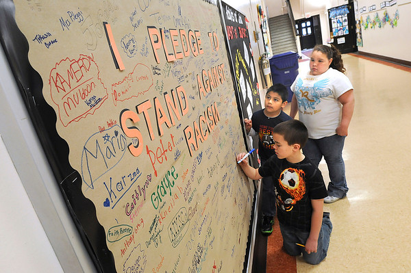 James Neiss/staff photographerNiagara Falls, NY - Maple Avenue Elementary students, from left, Xander Kraus, 10, Mateo Orfano, 8 andJasmin Easley, 11, sign a pledge to stand against racism.