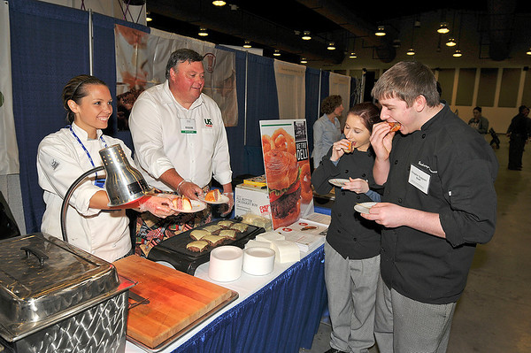 James Neiss/staff photographerNiagara Falls, NY - Culinary instructor Jessica Roth works with Charlie Martin of US Foods to make up some Pat LaFrieda Angus Beef Burger on a All-Butter Croissant Bun, to the delight of high school culinary students Taylor Mittner of Clarence and Zachary Stewart of Akron, who were attending the American Culinary Federation Northeast Regional Conference at the conference Center Niagara Falls on Saturday.