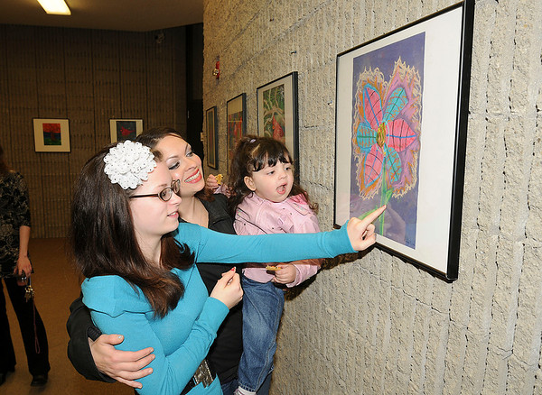 James Neiss/staff photographerNiagara Falls NY - Cataract Elementary 6th grader Angelica Sullivan, 12, shows off her artwork to her mother Elizabeth Villagomez and sister Isabel Villagomez, 2, during an artists reception at the Earl Brydges Public Library. Students from both Gaskill Prep and Cataract Elementary participated.