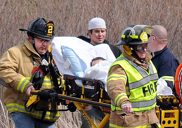 James Neiss/staff photographerNiagara Falls, NY - A concerned man looks on as Lewiston #2 and Mercy Flight personnel carry a young burn victim to a waiting helicopter that landed in a field at the corner of Walmore and Upper Mountain Roads for transport to Childrens Hospital.