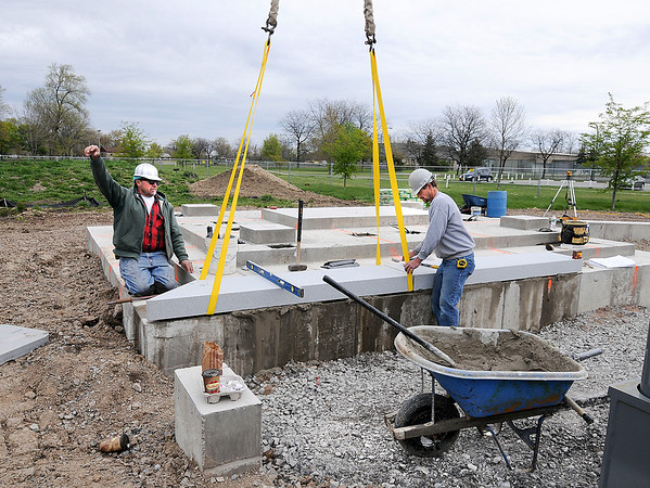 James Neiss/staff photographerNiagara Falls, NY - Stone Erectors Marik Chronis and Don Davis with the Rock of Ages Corp., place the first pieces of granite on the Niagara Falls Veterans Memorial at Hyde Park.