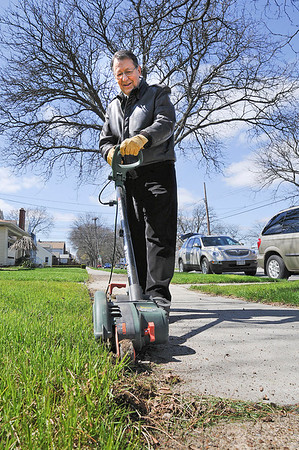 James Neiss/staff photographerNiagara Falls, NY - Working on the Edge: Vince Pellegrino of Niagara Falls, edges the sidewalk for his daughter and her elderly neighbor on Linwood Avenue.