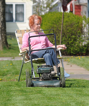 James Neiss/staff photographerNiagara Falls, NY - Bonnie Kyler takes a break and enjoys the summer like sunshine and temperatures after cutting the grass at her 72nd Street home on Monday.