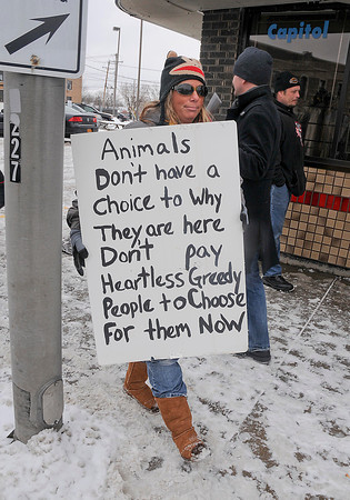 James Neiss/staff photographerNiagara Falls, NY - Cherrel Leidenfrost of Wilson walks with protesters organized by Animal Allies of WNY, at a protest in front of the Main Street business of SPCA board member Russ Petrozzi on Saturday.