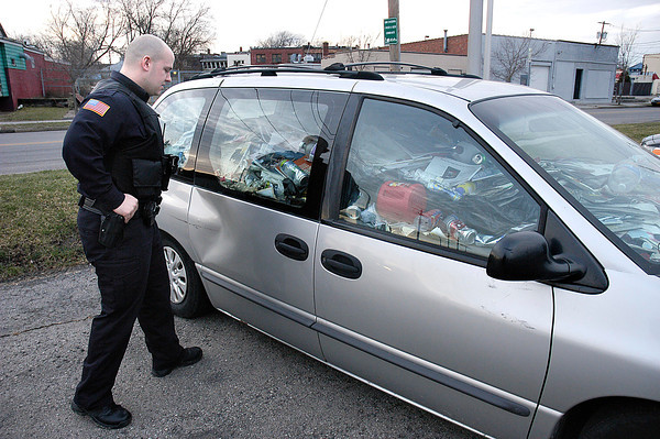 James Neiss/staff photographerNiagara Falls, NY - Hoarder Car: Niagara Falls Police Officer Josh Miller, said he has never run across a situation like this car that is filled almost to the brim with debris, parked in a City parking lot on Portage Road next to the YMCA. Miller, said this vehicle is definitely unsafe to drive and that he was going to consult with a traffic officer about the situation.
