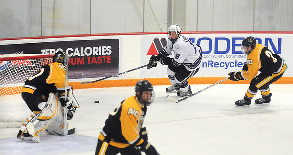 James Neiss/staff photographerLewiston, NY - Niagara University hockey player #16 Chris Lochner takes the puck behind the AIC Yellow Jackets goal during the first period of game action at Dwyer Arena.