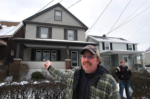 James Neiss/staff photographerNiagara Falls, NY - John Overbeck and his son Michael, 16, stand in front of their Woodlawn Avenue home. Overbeck purchased his home through Neighborhood Housing Services.