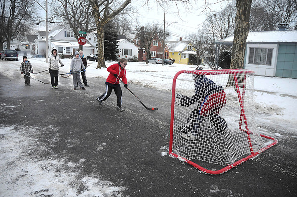 James Neiss/staff photographerNiagara Falls, NY - Michael McDonald, 12, takes a shot at goalie Cameron Faccini during a street hockey game in front of his Roselle Avenue home. McDonald, said they enjoy playing outside after school.