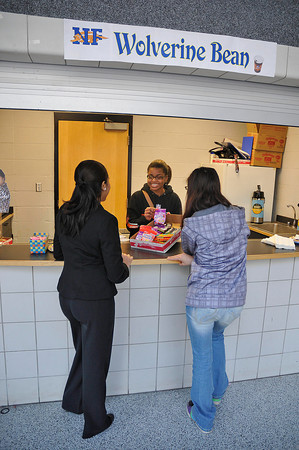 James Neiss/staff photographerNiagara Falls, NY - Niagara Falls High School entrepreneur class student Jabrea Drake, center, tries to make a sale by showing off some treats to customers Adrianna Ryles, left, and Danielle Rubin, right, at the Wolverine Bean cafe at the high school. The entrepreneur class also operates a cookie stand, the school store, a pizza shop and the Wolverine clothing store inside the school.