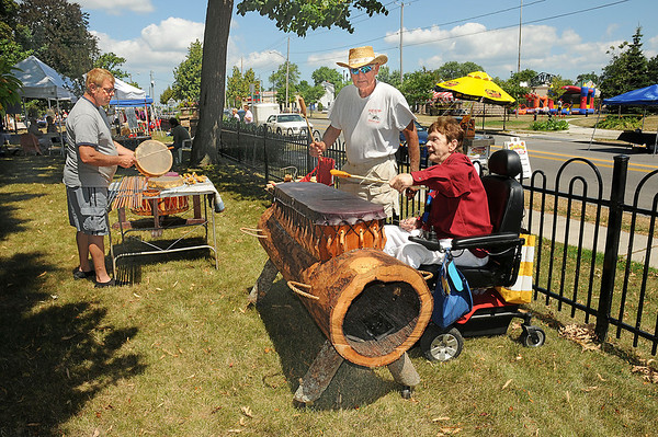 James Neiss/staff photographerNiagara Falls, NY - Clifford Bussard, left and Sandy Lillis, right, beat on drums created by Native American artist Pete Bissell, center, during Arts in the Park between the Niagara Falls Memorial Medical center and Niagara Arts and Cultural Center at Schoelkopf Park.