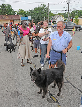 James Neiss/staff photographerNiagara Falls, NY - Off duty mailman Elliot Arce bravely wears his uniform for all the dogs to see as he waits to get his dog Tyson vaccinated for the Parvo Virus. Niagara Falls residents were invited to the corner of 18th Street and Linwood Avenue on Thursday for the free shot sponsored by the SPCA of Niagara.