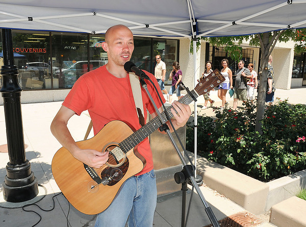 "James Neiss/staff photographerNiagara Falls, NY - Musician Brent Persia plays for tourists as part of ""Tunes @ Noon"" on Old Falls Street."