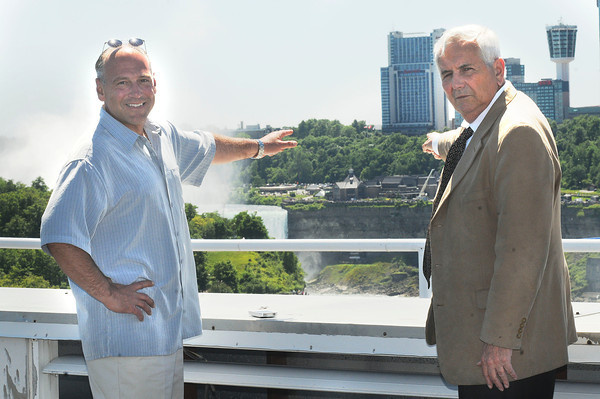 James Neiss/staff photographerNiagara Falls, NY - One Niagara Managing Partner Paul Grenga, left, and President Tony Farina point to their available view of wire-walker Nik Wallenda's historic walk. One Niagara is opening up the top floor for guest viewing on Friday.