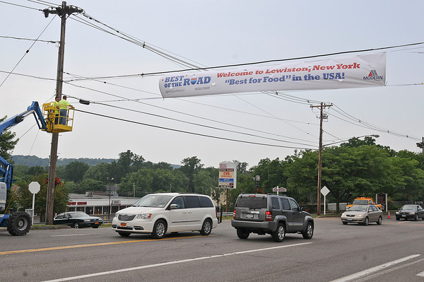 """James Neiss/staff photographerLewiston NY - Lewiston DPW workers Larry Wills and Anthony Mang hang a banner over Center Street after being voted """"Best for Food"""" in the USA by Rand McNally's Best of the Road."""